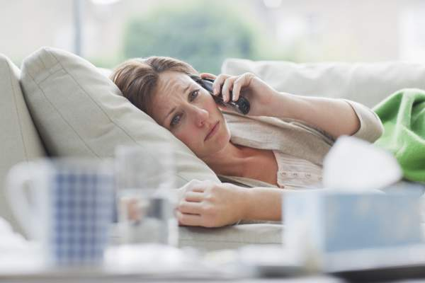 Woman laying on her couch and staring ahead while listening to someone on the phone