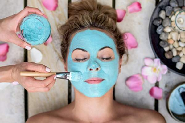 Woman getting a face mask at a spa.
