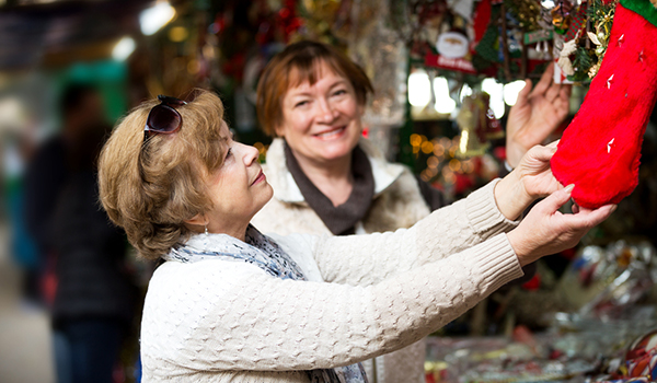 Smiling women hanging holiday decorations.
