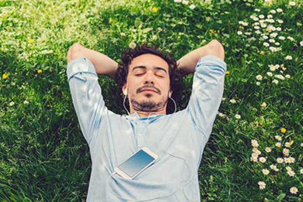 Man lying in the grass listening to music.