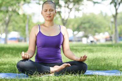 Young woman with short hair practicing yoga in park.