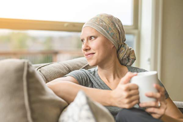 Young adult female cancer patient sipping tea.