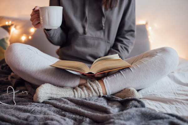 Girl drinking hot tea and reading book in bed and wearing comfortable clothing