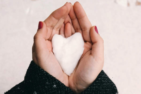 woman's hands cupping heart shaped snow