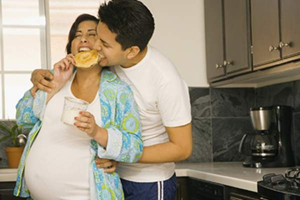 Expectant couple playful eating in kitchen.