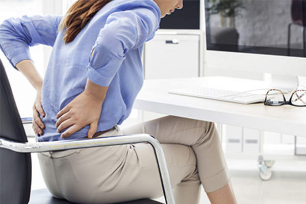Business woman with low back pain in chair at work.