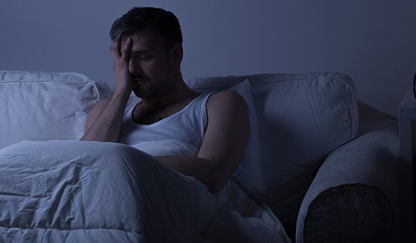 man with migraine in bed in dark room image