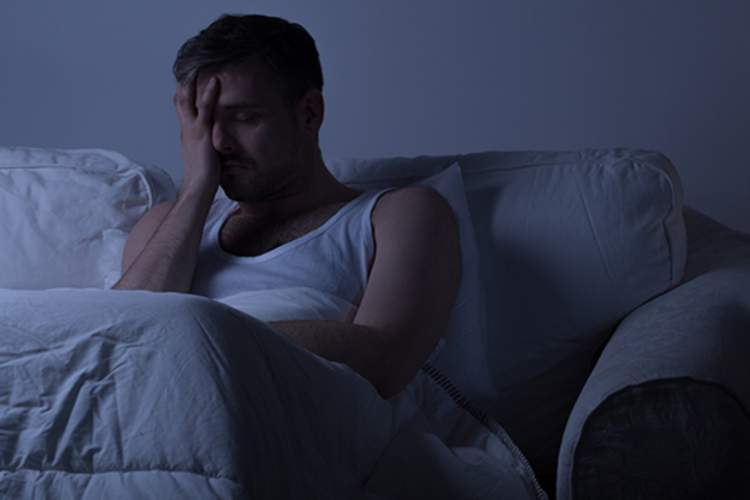 man with migraine in dark room image