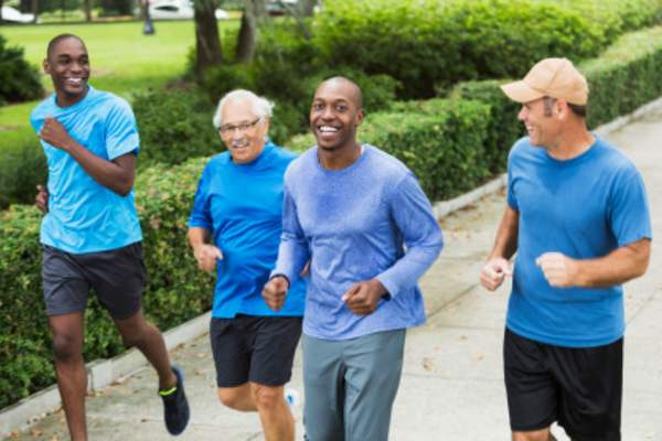 Smiling men jogging and wearing blue shirts for colon cancer awareness.