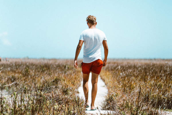 man walking to beach wearing shorts and t-shirt