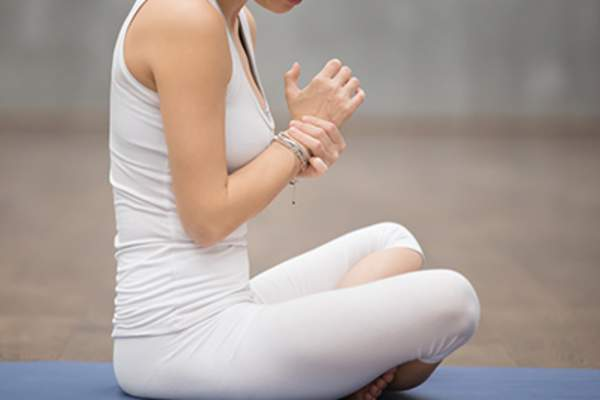 Young woman in exercise clothes holding her wrist in pain.