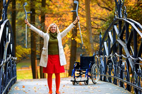 Happy woman raising her crutches.