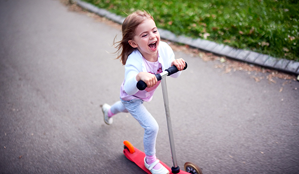 Girl riding a push scooter.