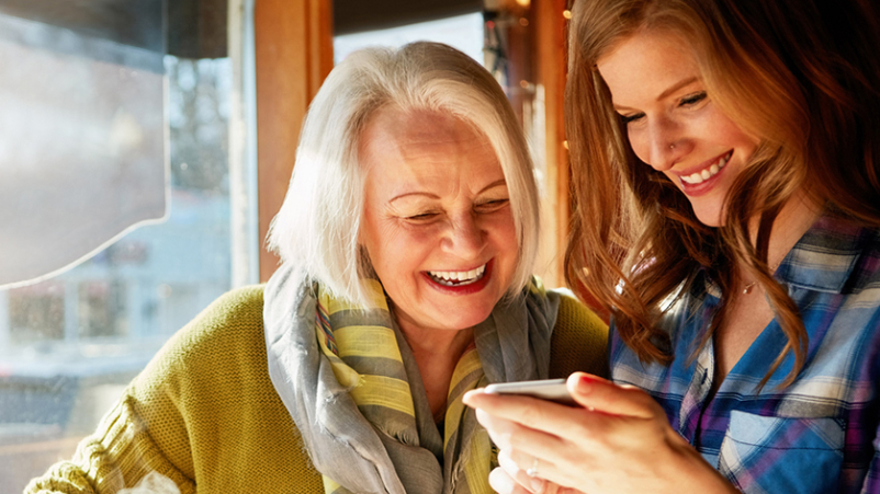Adult daughter and elderly mother smiling looking at photos.