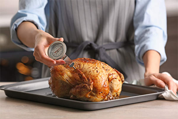 Woman measuring temperature using a meat thermometer in a baked chicken.