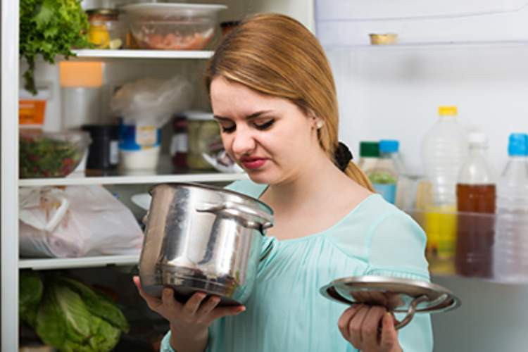 Young woman smelling spoiled food in pan.