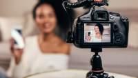 显示年轻vlogger的DSLR照相机屏幕特写镜头