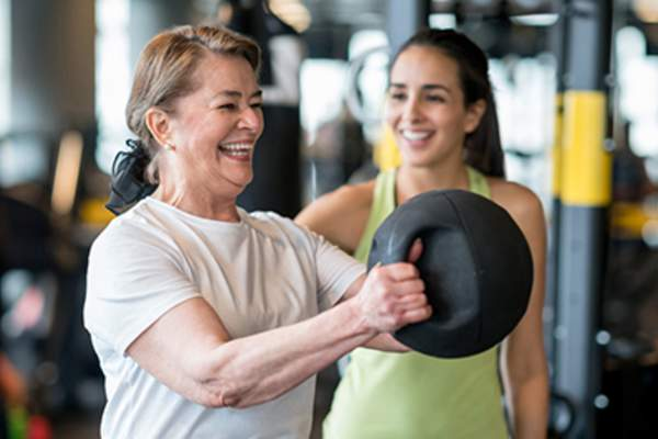 Smiling older woman working out with trainer.