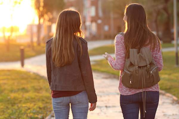 Female friends walking and talking on park path.