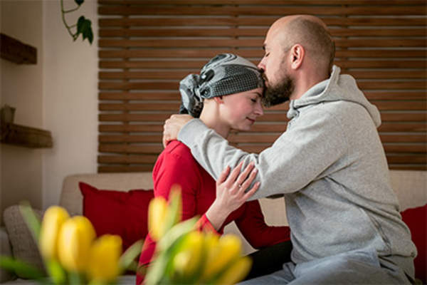 Husband kissing his wife during her cancer treatment.