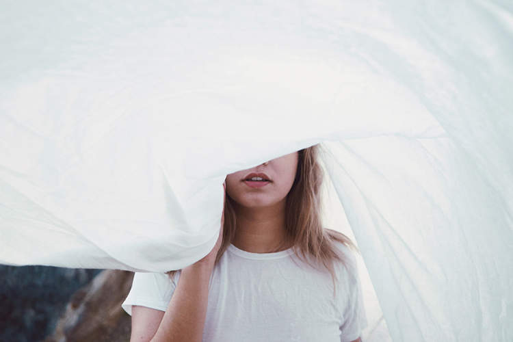 Woman with a sheet in front of her face