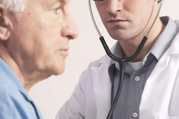 Doctor listening to senior man's heart with stethoscope.