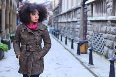Stylish woman wearing a winter coat outdoors.