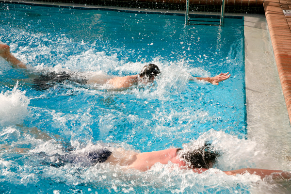 Two-swimmers-racing-to-touch-the-wall-in-a-pool
