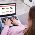 Thumb-woman-sitting-on-sofa-shopping-footwear-online-on-laptop