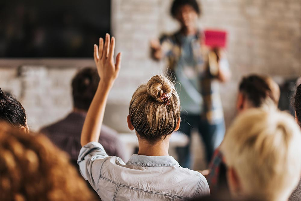 Student raising hand in classroom 1000px W