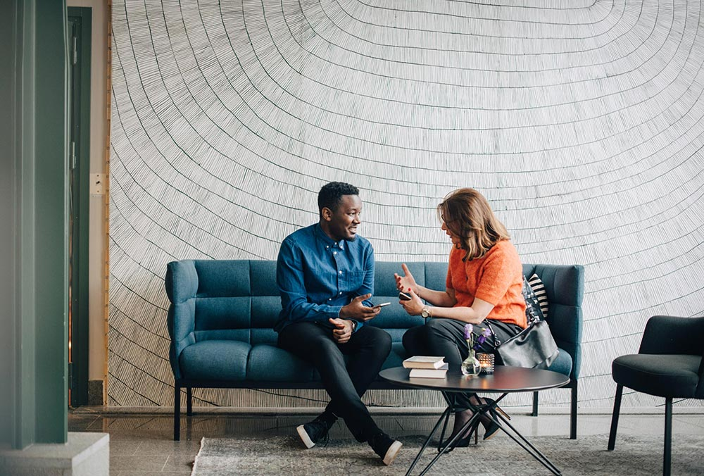 Man and women in conversation in office 1000px W