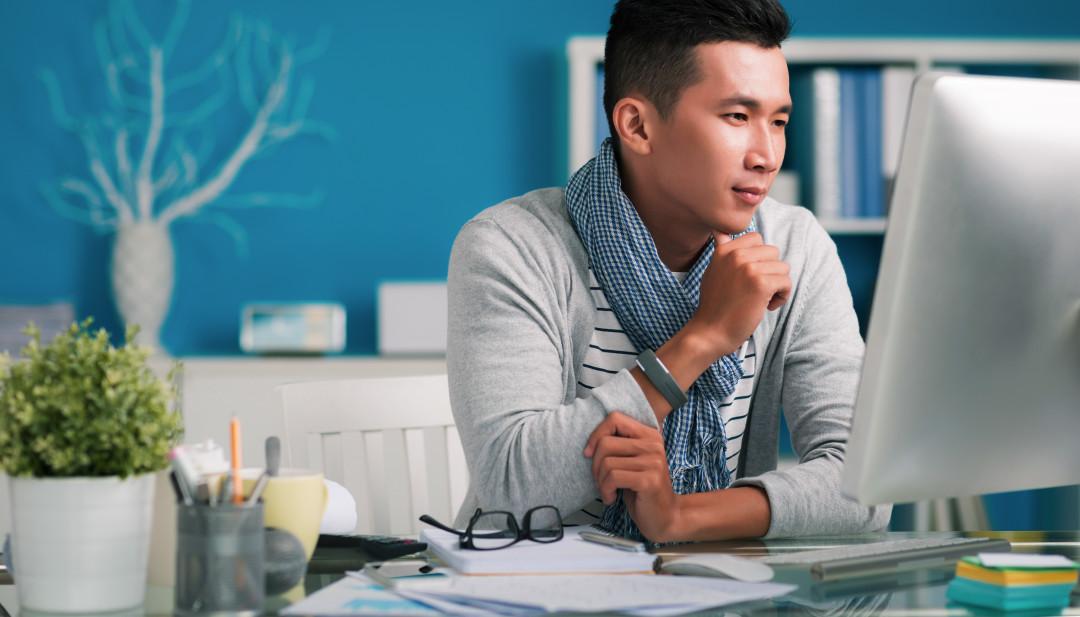 Asian man looking at computer