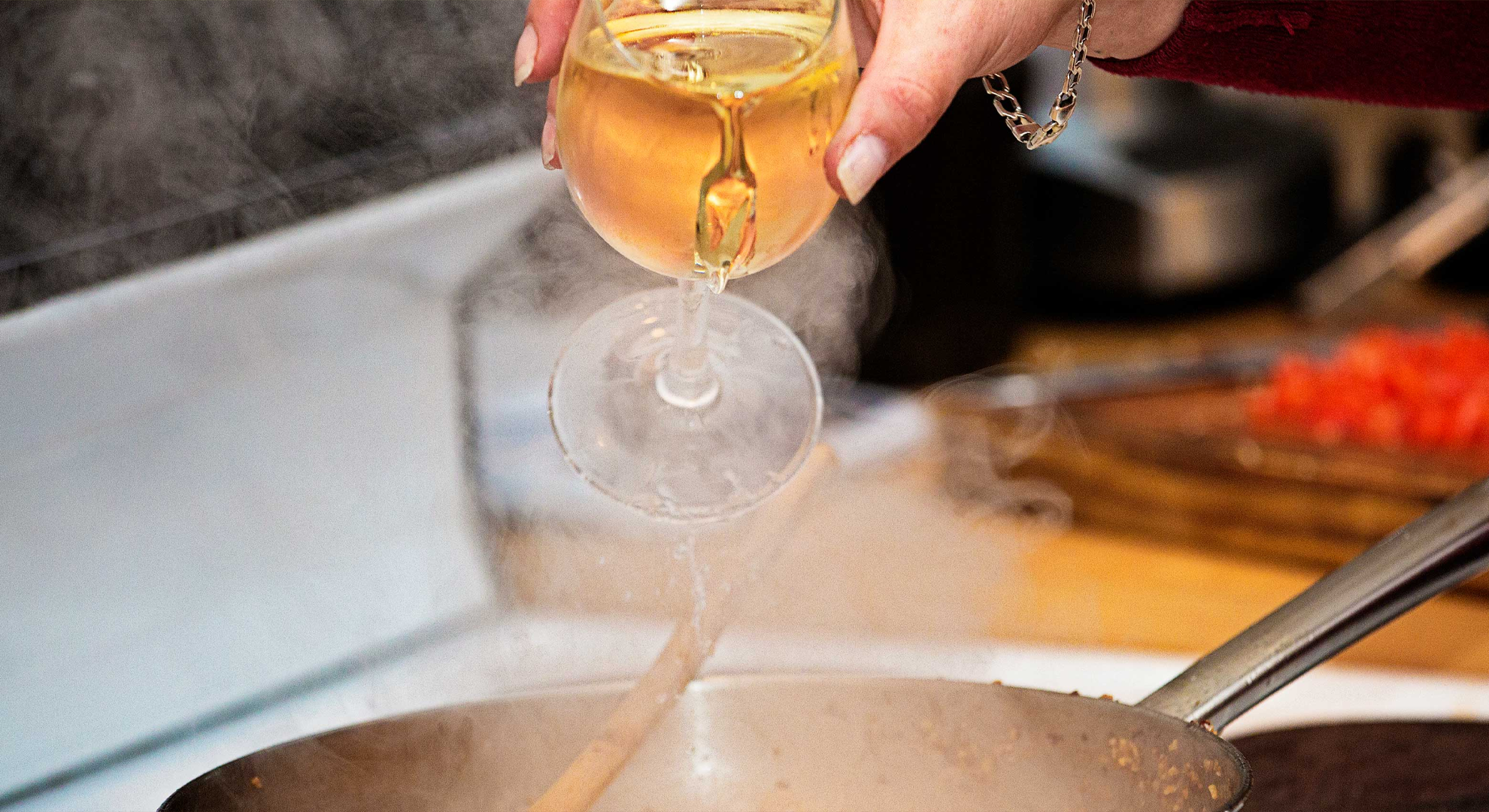Wine being poured into a cooking pot over a stove.