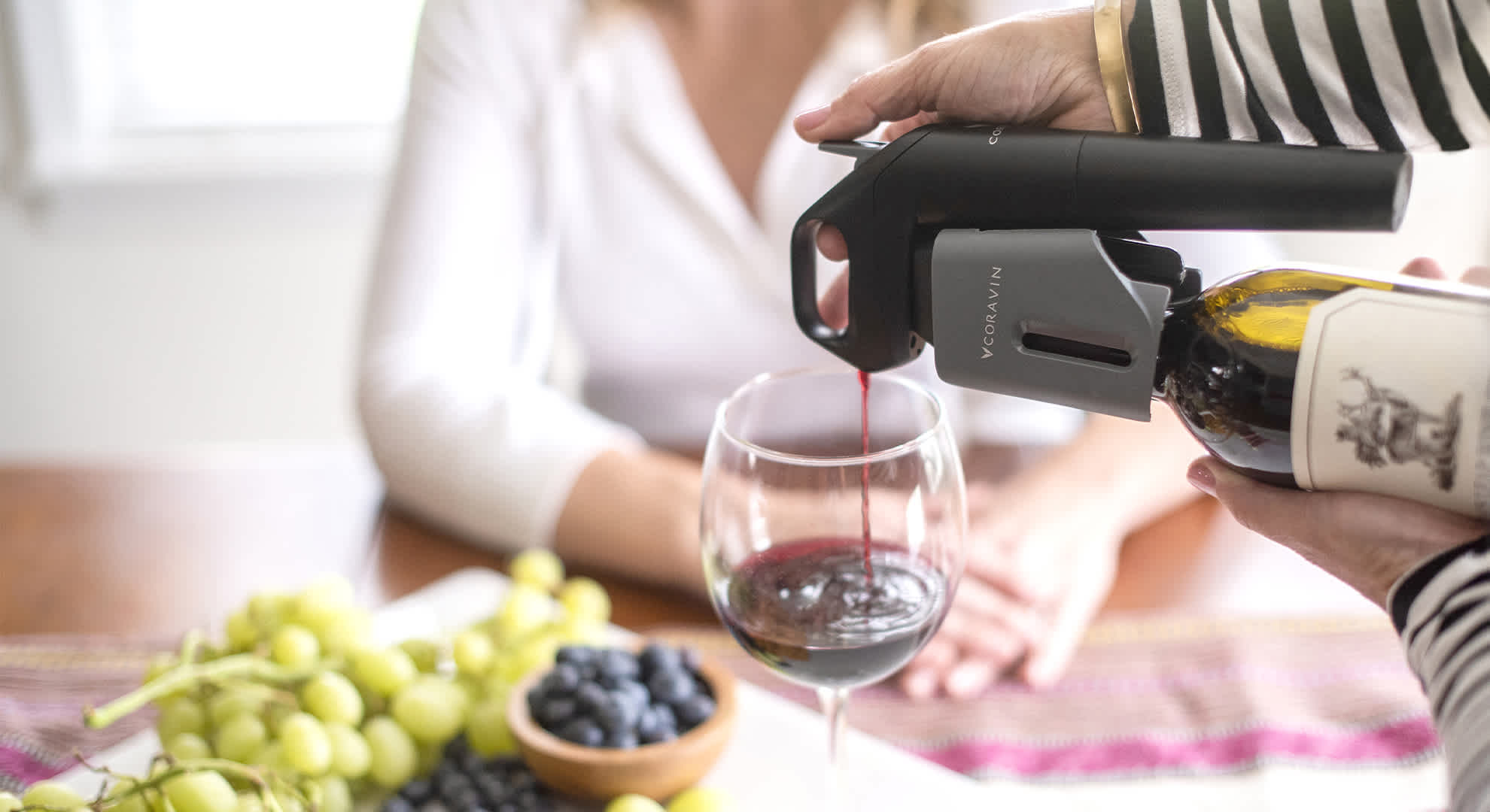 A woman pouring wine into a glass using the Coravin Model Three System with grapes, blueberries, and another woman in the background.