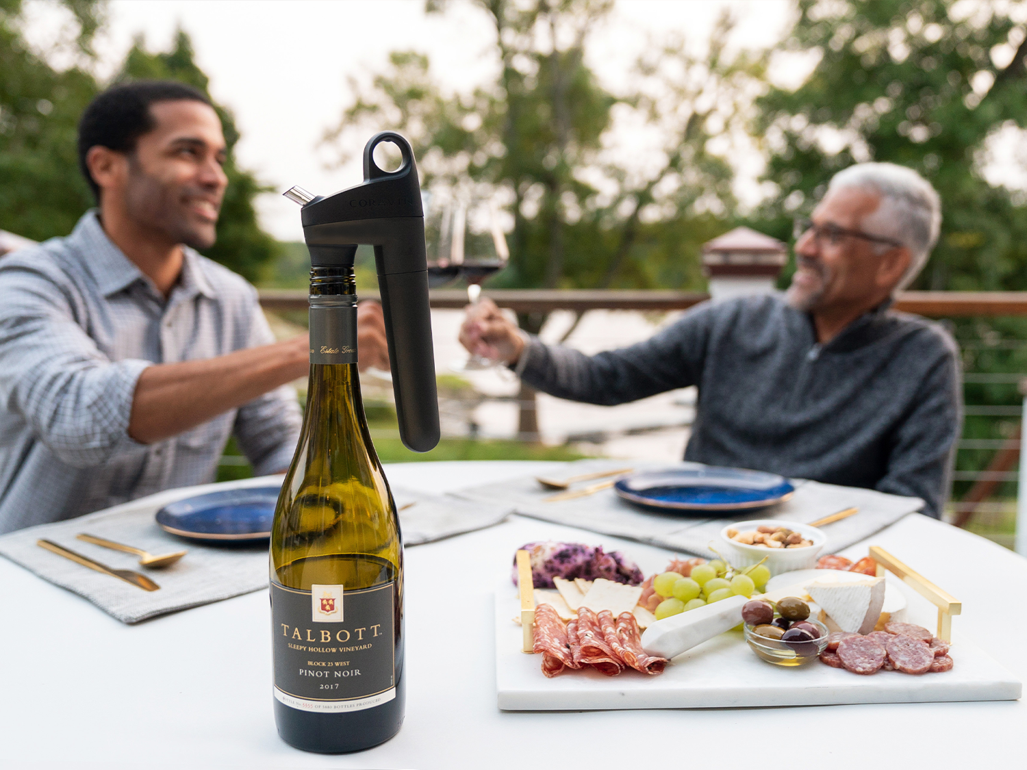 Pivot Wine Preservation System on bottle with man and son enjoying wine in the background