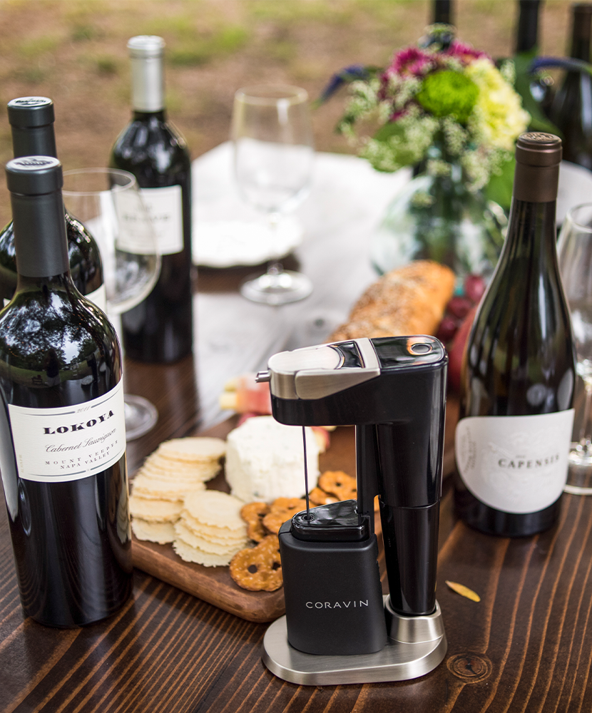A variety of wine bottles and snacks on a table outdoors, featuring a Coravin Model Eleven standing in a base.