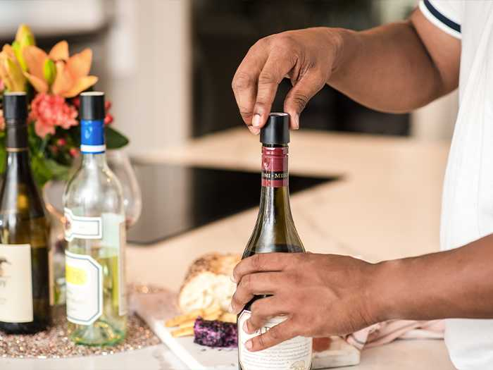 Person at a table spread of charcuterie and wine, screwing a Coravin Screw Cap onto a wine bottle.