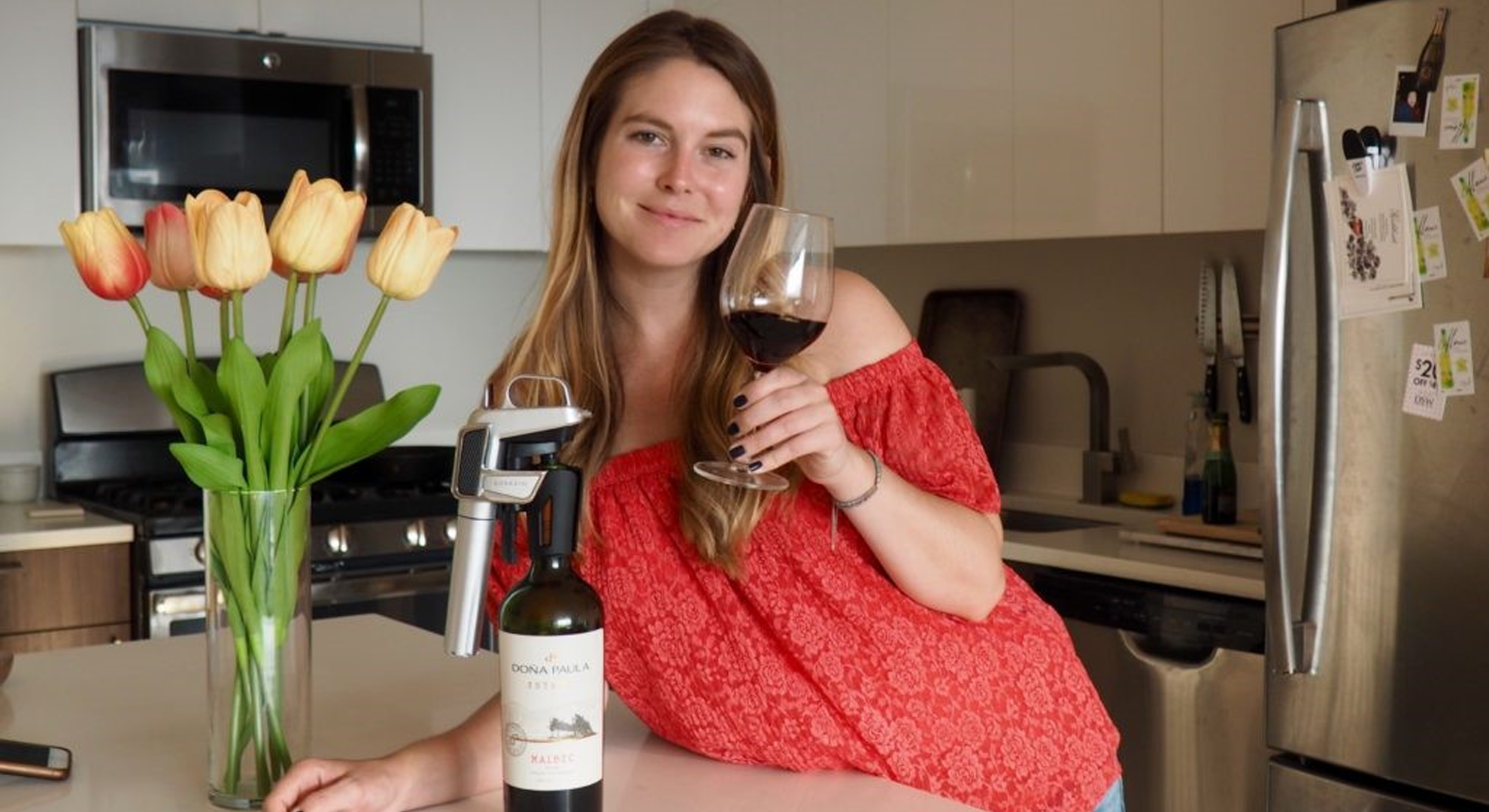Chelsie Petras de Chel Loves Wine tenant un verre de vin et un système Coravin placé sur une bouteille de vin rouge.
