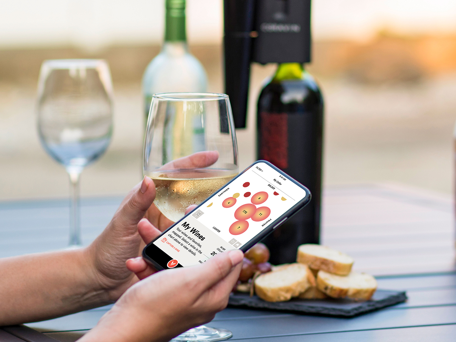 A person holding a glass of wine and a phone that features the Coravin Moments App flavor map screen, with the Coravin Model Eleven Wine Preservation System on bottle in the background.