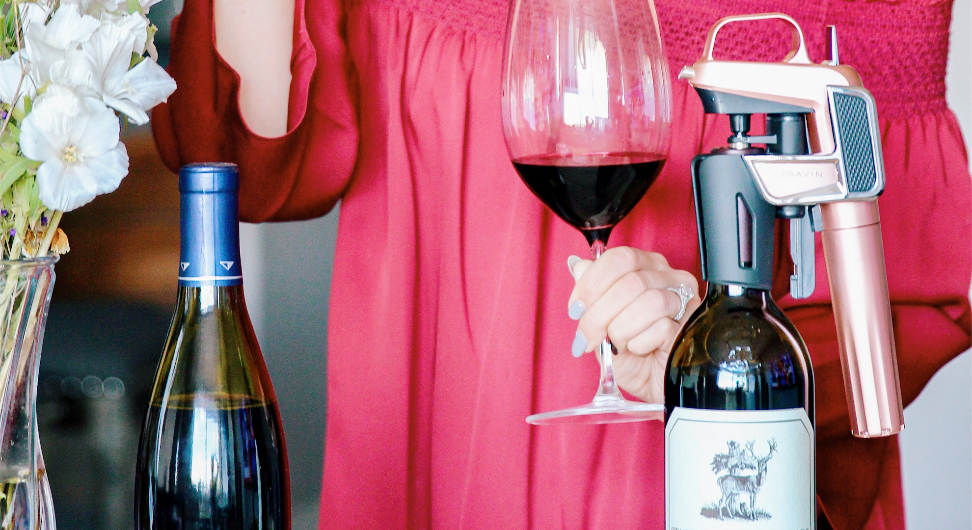 Woman holding a glass of red wine featuring a Coravin Wine Preservation System on bottle.