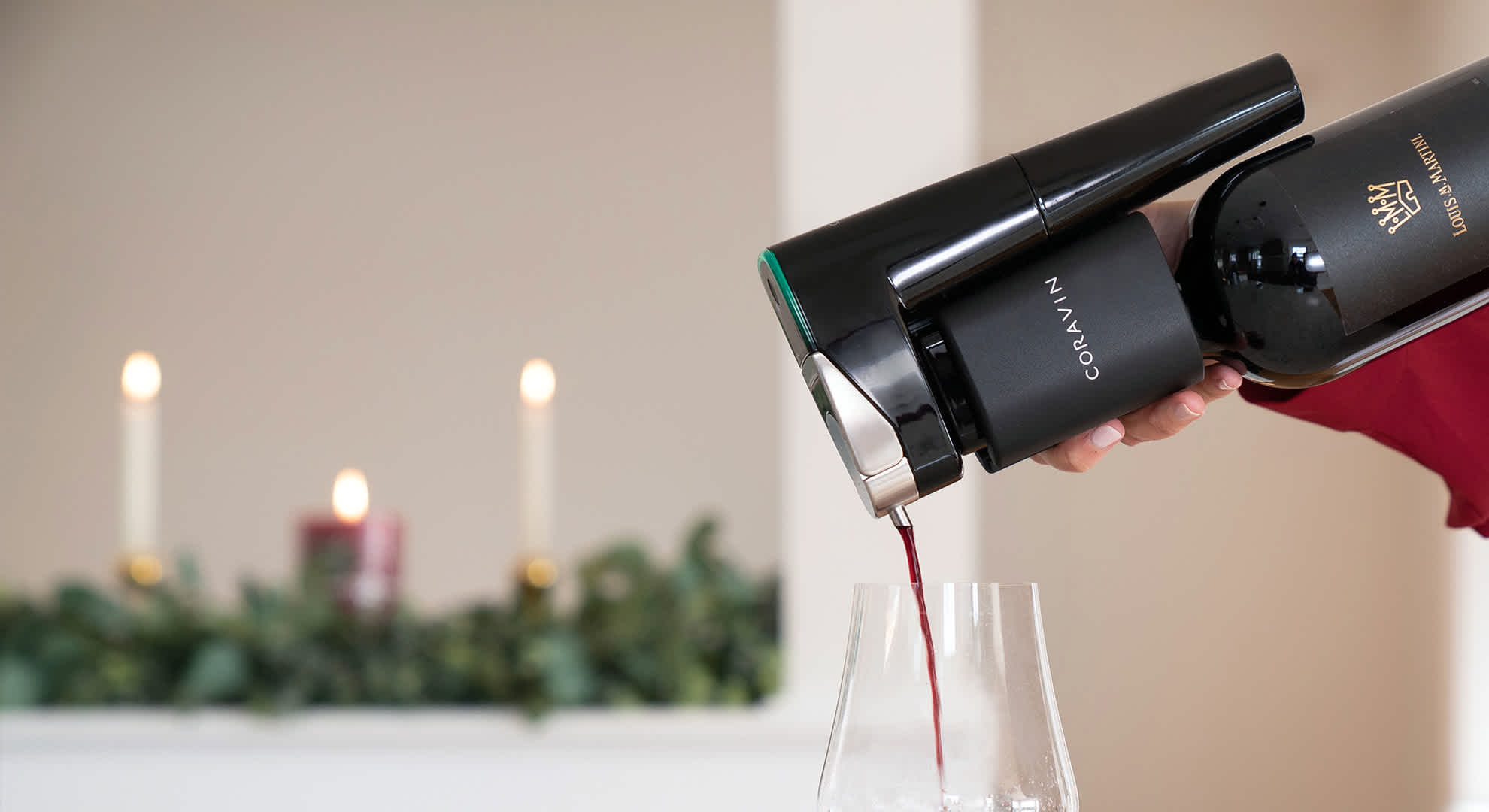 Pouring red wine with the Model Eleven Wine Preservation System in a holiday setting
