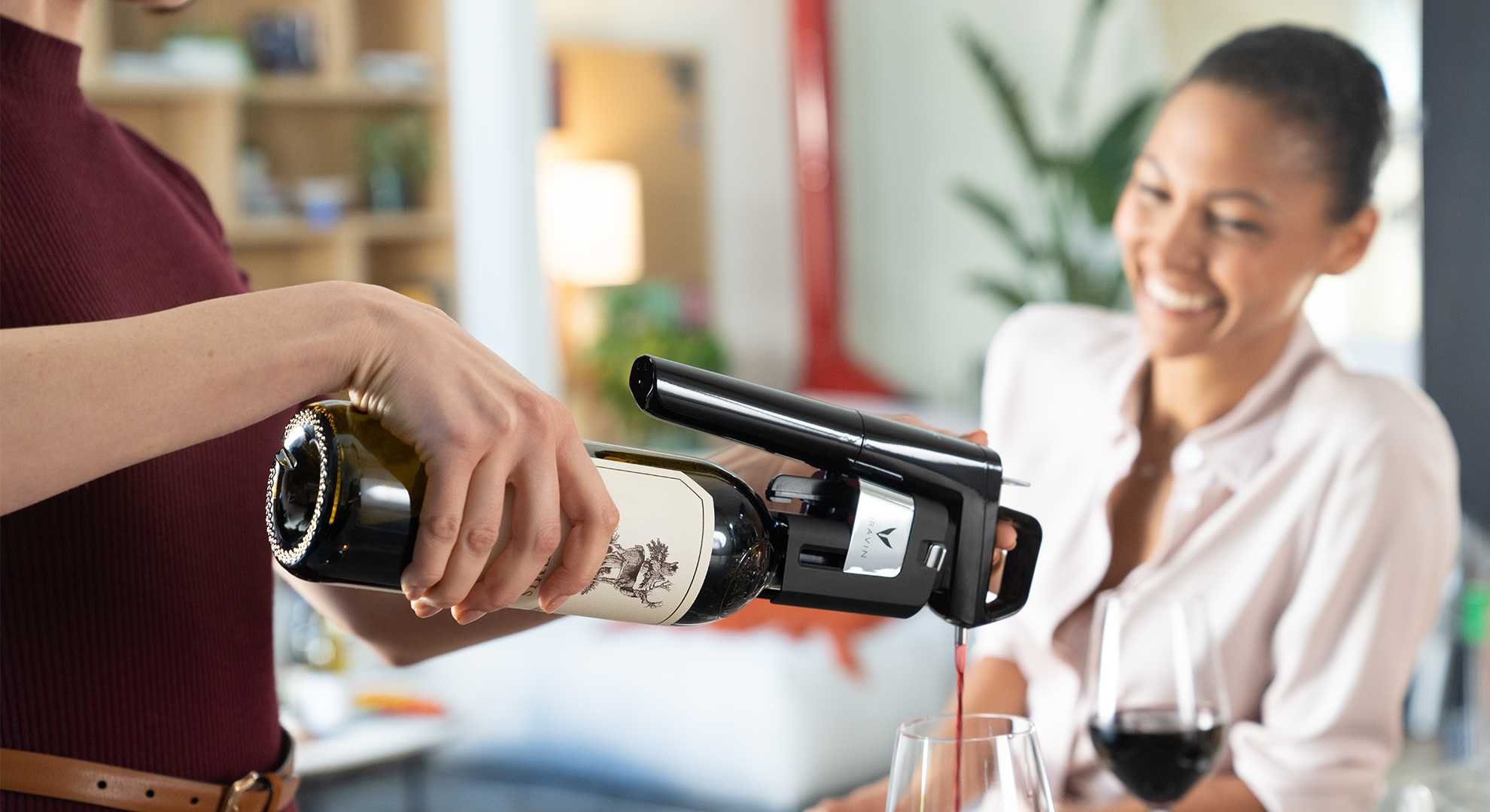 Young, professional woman smiling as a glass of red wine is poured using a Coravin Wine Preservation System.