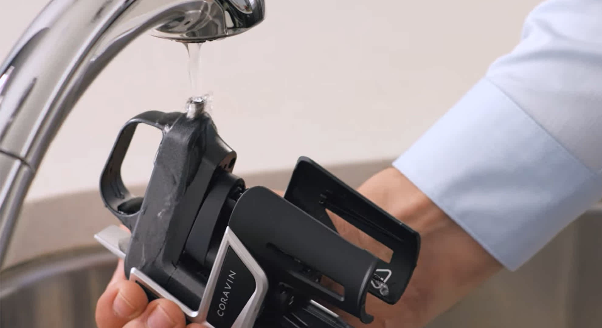 A Coravin Wine Preservation System is held under a running tap