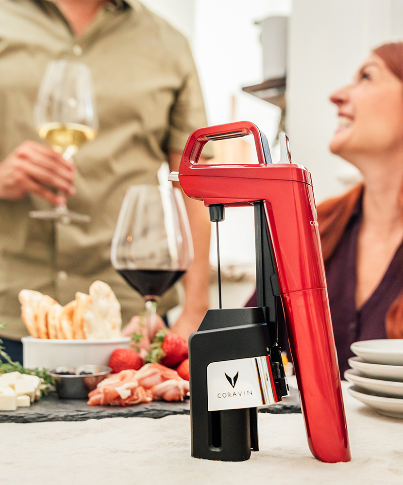 A couple drinking red and white wine with charcuterie, featuring a standing Coravin Model Six in Candy Apple Red.