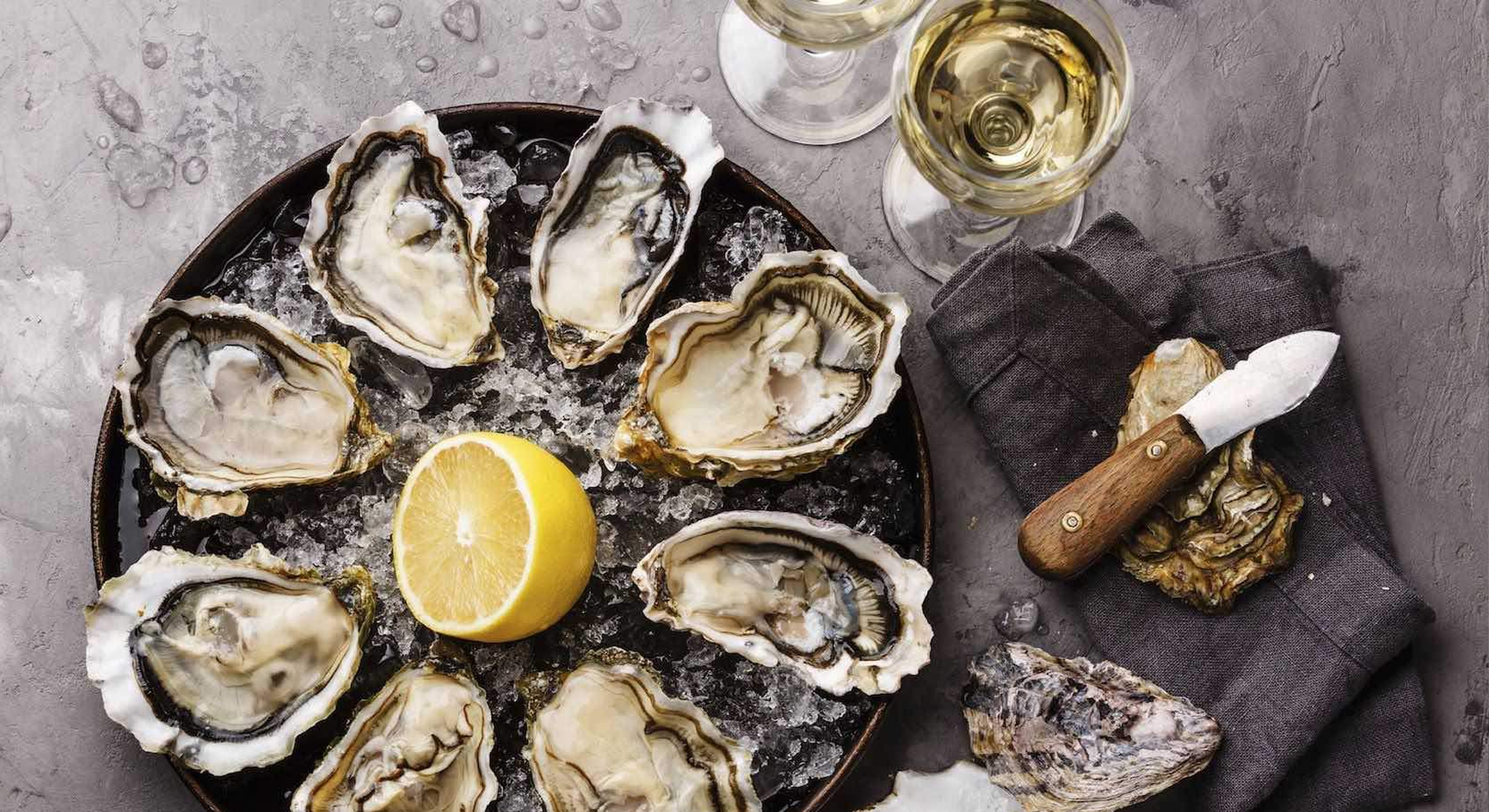 Oysters and lemon on a bed of ice, with an oyster shucking knife and two glasses of white wine.