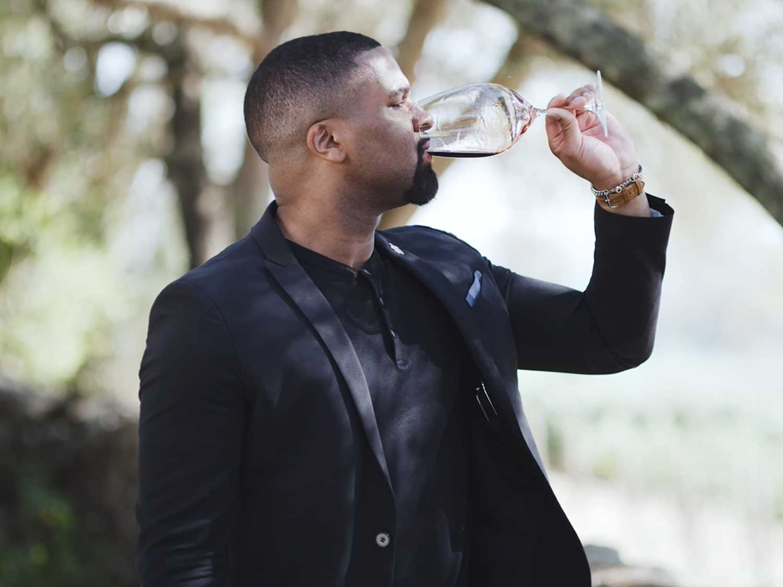 Man drinking wine outside.