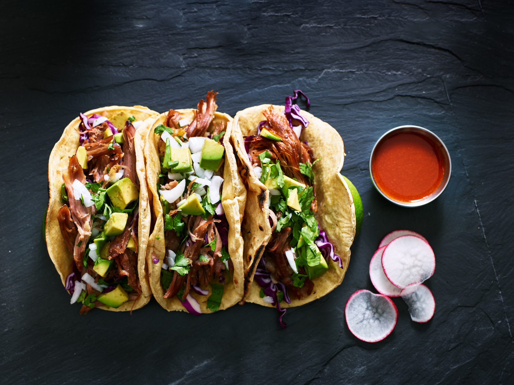 carnitas tacos with avocados raddish and cabbage