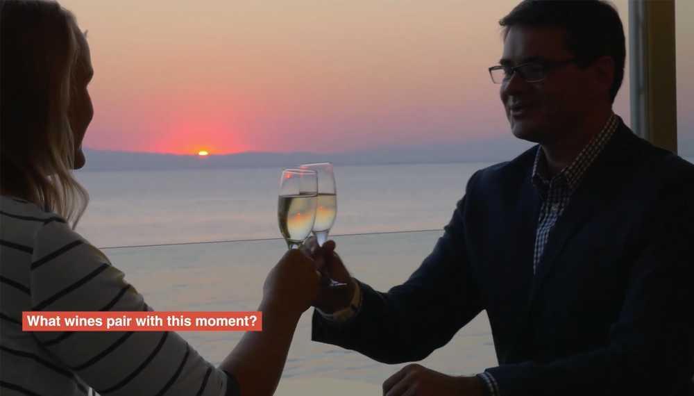 Un couple en train de trinquer au vin blanc avec un coucher de soleil et l'océan en arrière-plan.