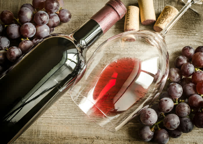 red wine in a glass next to a wine bottle and grapes.