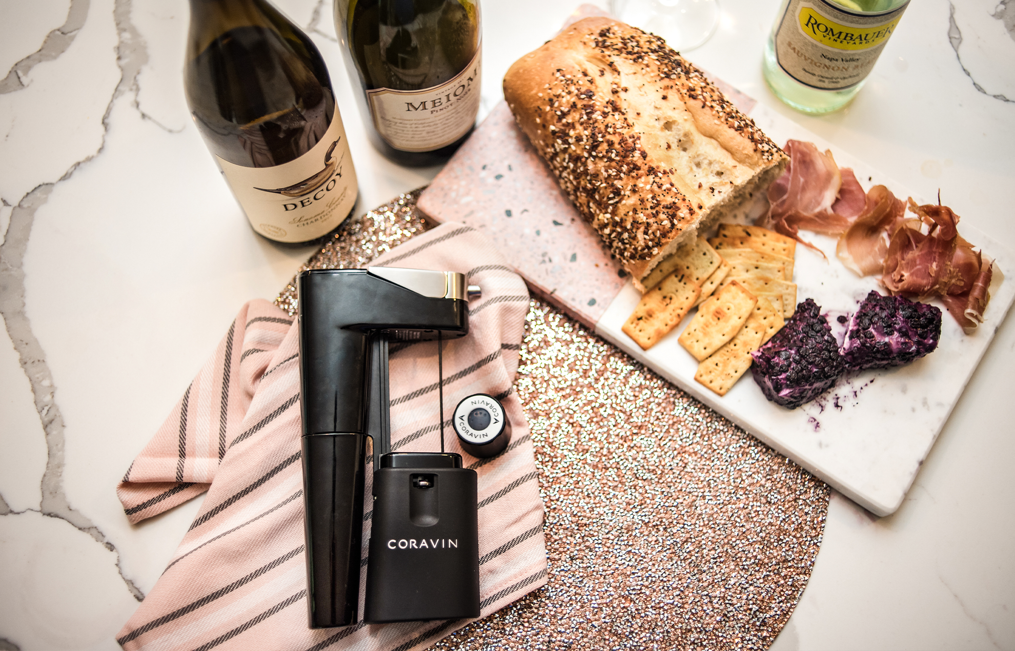 Spread of wine and charcuterie on a table with a Coravin Model Eleven and Coravin Screw Cap.